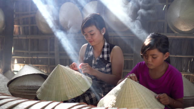 4k footage low light scene of two sibling vietnamese craftsman making the traditional vietnam hat in the old traditional house in ap thoi phuoc village, cantho province, vietnam, traditional artist concept - embroidery stock videos & royalty-free footage