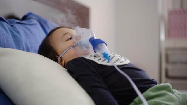 4k aufnahmen von einem niedlichen kleinen jungen mit inhalationsmaske auf dem bett liegen - sichtbarer atem stock-videos und b-roll-filmmaterial