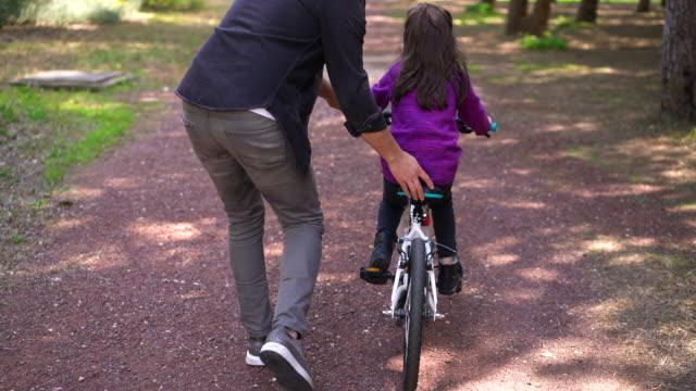 vídeos de stock, filmes e b-roll de 4k imagens de um pai ensinando sua filha a andar de bicicleta no parque - montar