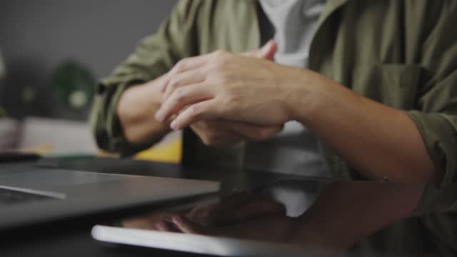 vídeos de stock, filmes e b-roll de 4k filmagem de homem adulto asiático tendo uma dor na mão.massagem na mão - dor