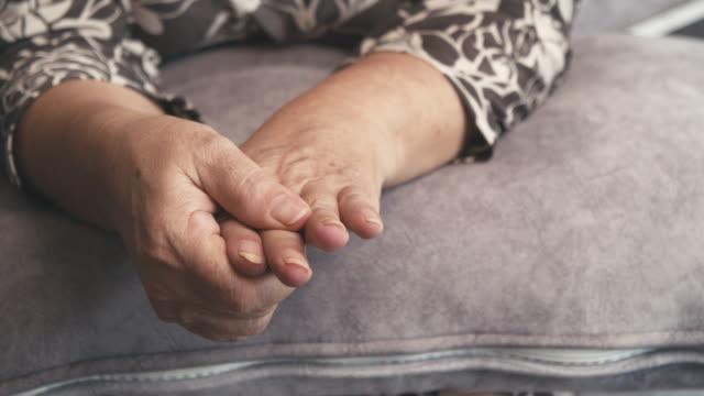 手の痛みを持つソファに座っているアジアのシニア女性の4k映像 - マッサージする点の映像素材/bロール