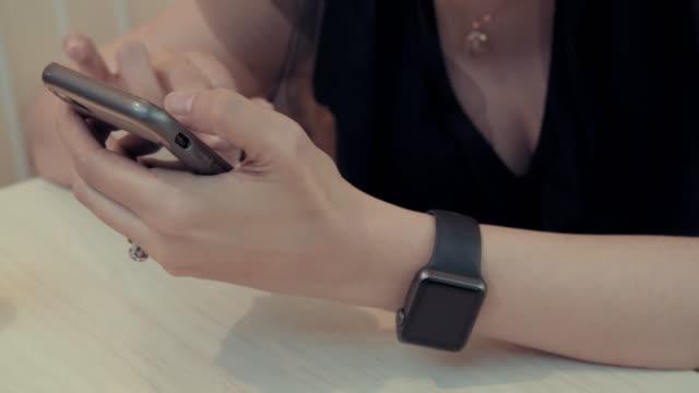 vídeos y material grabado en eventos de stock de 4 imágenes de k de mujer asiática a mano utilizando smartphone sobre la mesa en casa .chatting con personas y cheque en su cuenta de red social - espalda humana