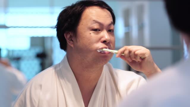4 k aufnahmen von closeup asiatischer mann zähneputzen mit einer zahnbürste im bad vor spiegel morgens beim aufwachen auf das luxus-hotel schlafzimmer, lifestyle und freizeit-konzept - zahnbürste stock-videos und b-roll-filmmaterial