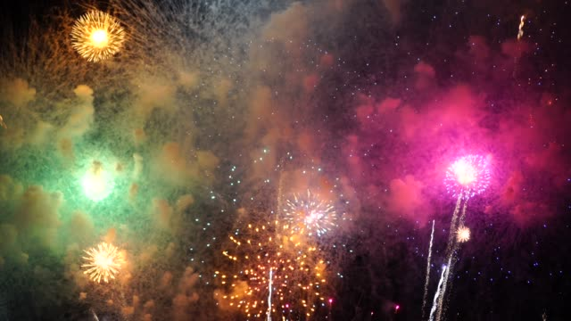 4k footage of fantastic multicolor fireworks with smoke over the night sky background, celebration concept, - fashion show stock videos & royalty-free footage