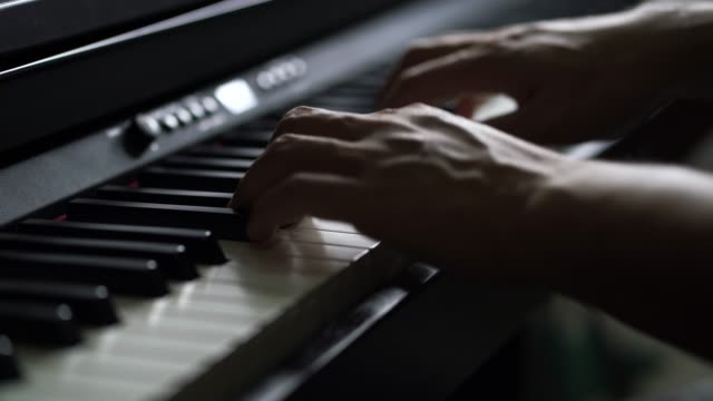 4k footage of man han playing on digital piano - compositore video stock e b–roll