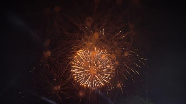 4 k Aufnahmen von mehrfarbigen Feuerwerk mit über Rauchen und Scheinwerfer die Nacht Himmelshintergrund, Feier