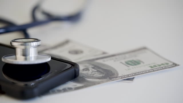 vídeos de stock, filmes e b-roll de 4 cenas k de estetoscópio... com dinheiro e smartphone. conceito de saúde - falência