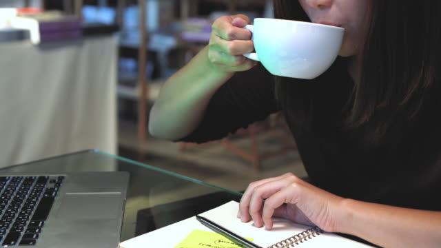 4k footage scene closeup hands of asian businesswoman working and writing on post-it notes in notebook with green screen laptop and drinking coffee in coffee cafe, lifestyle and business concept - adhesive note stock videos & royalty-free footage
