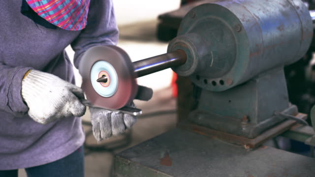4k footage scene closeup of angle grinder hand holding and grinding the spare parts of metal gear in lathe metalworking factory, industry and machine concept - metal clip stock videos and b-roll footage