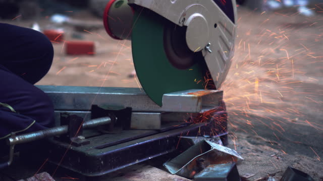 4k footage scene closeup of hands using angle grinder cutting and grinding steel parts of metal in metal factory, industry and machine concept - erezione video stock e b–roll