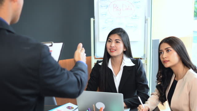 4k footage scene group of asian businessman assign a task to businesswoman working and discussing work plan project with teamwork at office, business and meeting success concept - human role stock videos & royalty-free footage