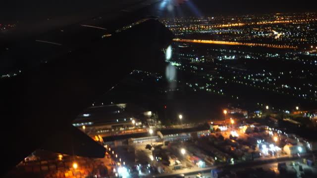 vídeos de stock, filmes e b-roll de cena de filmagem 4 k de avião sobrevoando a cidade à noite, antes prepare-se para pouso o conceito do aeroporto, viagens e transporte - asa de aeronave