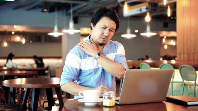 4k footage scene of Asian businessman in casual suit working and suffering with shoulder and neck pain in front of laptop at co-working space, Business health and office syndrome concept