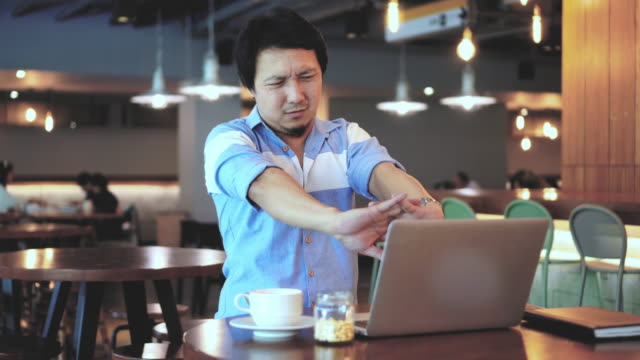 4k footage scene of asian businessman in casual suit working and suffering with arm stiffness in front of laptop at co-working space, business health and office syndrome concept - backache stock videos & royalty-free footage