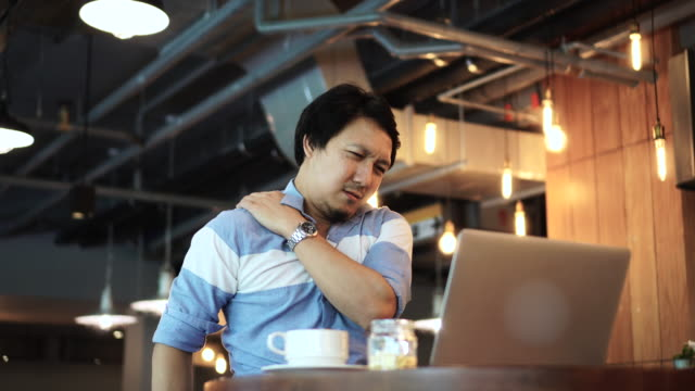 4k footage scene of asian businessman in casual suit working and suffering with shoulder and neck pain in front of laptop at co-working space, business health and office syndrome concept - postura video stock e b–roll