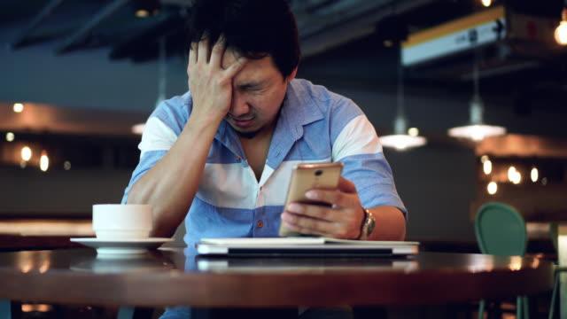 vídeos de stock, filmes e b-roll de cena de filmagem k 4 do empresário asiático em casual terno trabalhando e sofrendo de depressão com smartphone no trabalho co espaço, saúde business e salientar o conceito - deteriorado