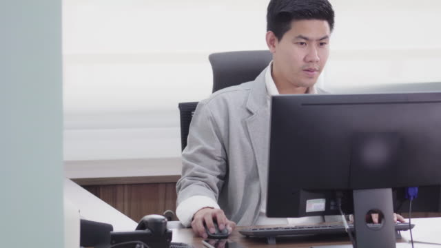 4k footage scene of asian businessman working with computer in office - administrator stock videos & royalty-free footage