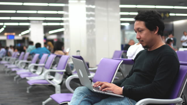 4k footage scene of Asian businessman working with laptop waiting for boarding time at the airport terminal, Business and Travel Lifestyle concept