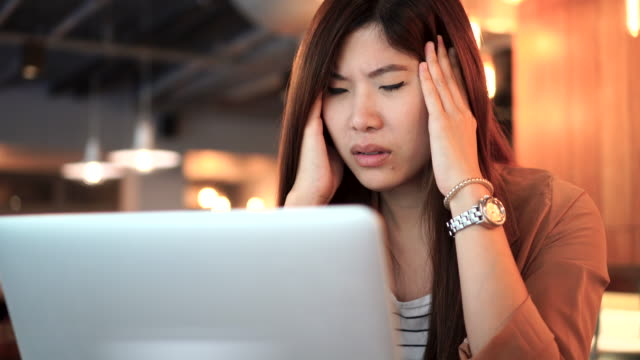 4k footage scene of asian businesswoman in casual suit working and suffering from depression in front of laptop at co-working space, business health and stress concept - headache stock videos & royalty-free footage