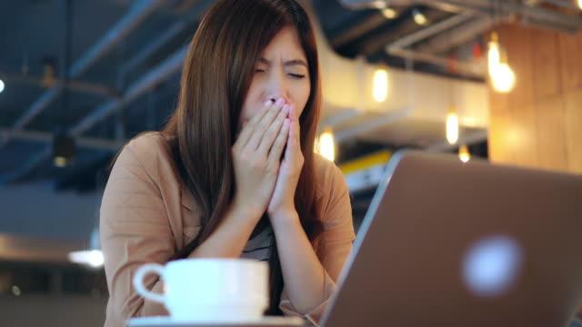stockvideo's en b-roll-footage met 4k footage scène van aziatische zakenvrouw in casual suit werken en hoesten in de voorkant van de laptop in co-working ruimte, business gezondheid en symptomen concept - chronische ziekte