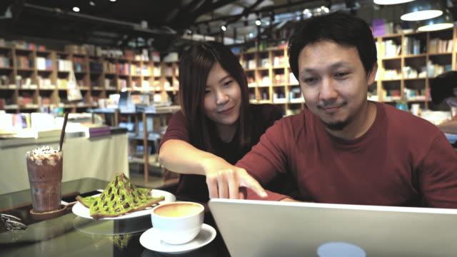 4 k beelden scène van Aziatische paar in casual pak praten en denken over werk met technologie laptop in de coffeeshop en moderne co-werkruimte, koppel en collega bedrijfsconcept