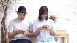 4k footage scene of asian couple in casual suit using their smartphone ignoring each other in modern co-working space, Lifestyle and leisure concept
