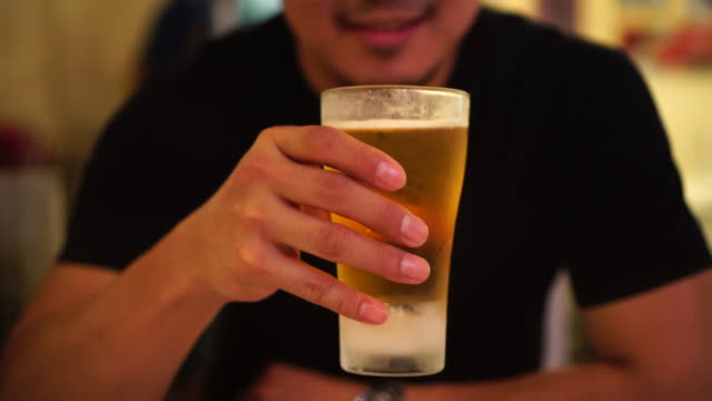 4k footage scene of asian man drinking a glasses of beer with happiness at bar and restaurant, relax and drink concept - pint glass stock videos & royalty-free footage