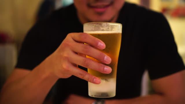 4 k filmmaterial szene des asiatischen menschen trinken ein glas bier mit glück in der bar und im restaurant, entspannen sie sich und trinken konzept - pint stock-videos und b-roll-filmmaterial