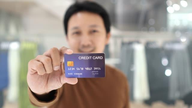 4 k 映像シーン男性司会者表示クレジット カード オンライン ショッピングのための百貨店、技術お金財布オンライン決済コンセプト、モックアップ クレジット カードで服屋の前にキャッシ� - 見せる点の映像素材/bロール