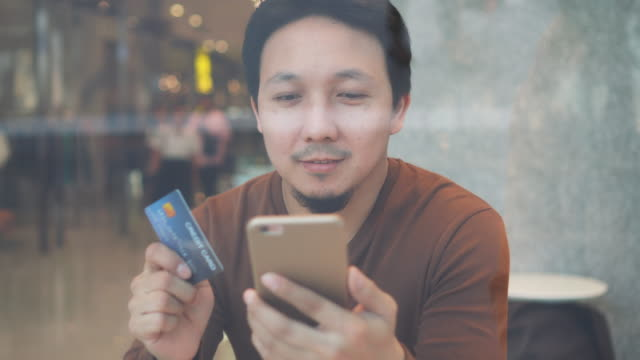 4k footage scene of asian man using credit card with mobile phone for online shopping cashless at co-working space in department store, technology money wallet and online payment concept, credit card mockup - online banking video stock e b–roll