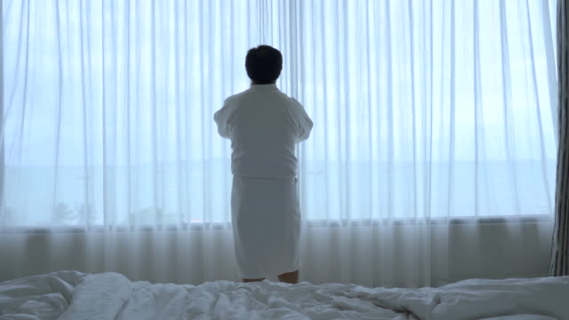 4k footage scene of asian man walking to open the curtain on the windows and stretch oneself in the morning when wake up in the luxury hotel bedroom, lifestyle and leisure concept - bathrobe stock videos & royalty-free footage