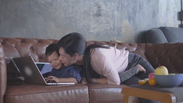 自己の現代の家にノート パソコンを再生しながら少年のキス アジアの母の 4 k 映像シーンが学習や学校、家族および幼年期の概念をホーム - 家の中点の映像素材/bロール