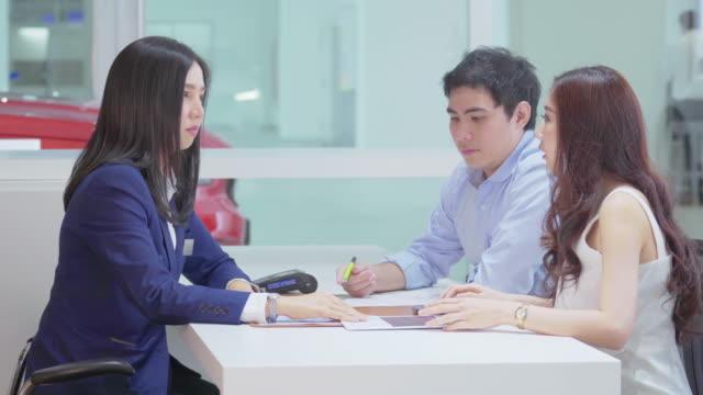 アジア販売員の4k 映像シーンショールームでお客様に説明 - 自動車ショールーム点の映像素材/bロール