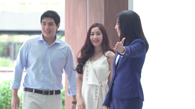 4k footage scene of asian saleswoman welcoming the couple customer in showroom - showroom stock videos & royalty-free footage