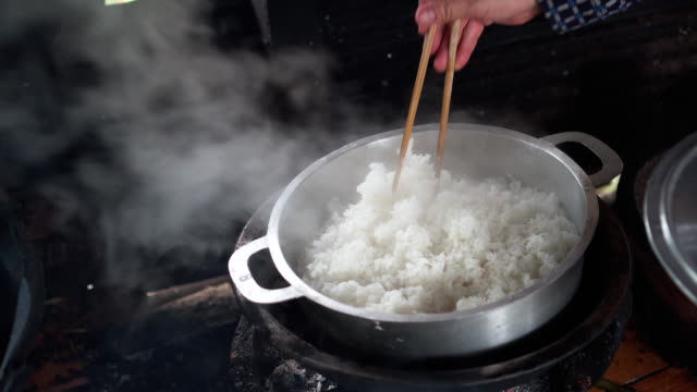 4k footage scene of asian woman cooking rice in pot with charcoal brazier and close the lid, preparing food and traditional cuisine concept - meal prepping stock videos & royalty-free footage