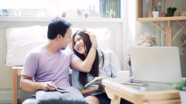 4k footage scene of asian woman in casual suit reading and sitting with man using smartphone full of sweet moment in modern co-working space, couple and lifestyle concept