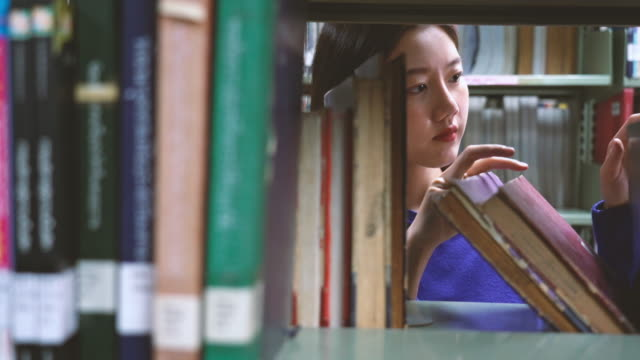 4k footage scene of asian woman searching the book in library - bookstore stock videos & royalty-free footage