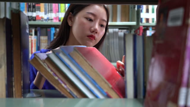 4k footage scene of asian woman searching the book in library - textbook stock videos & royalty-free footage