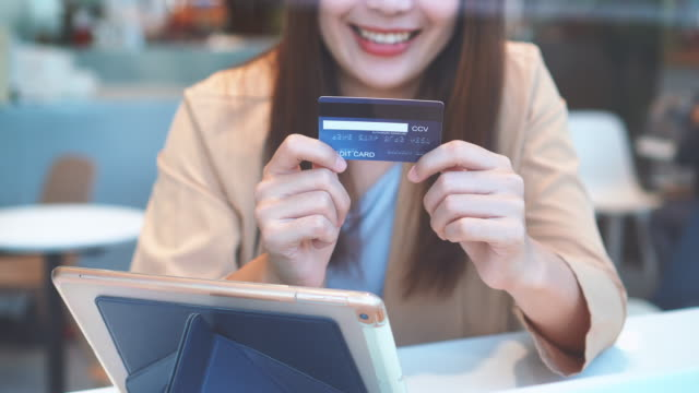 4k footage scene of Asian woman using credit card with tablet for online shopping cashless at co-working space in department store, Technology money wallet and Online payment concept, credit card mockup