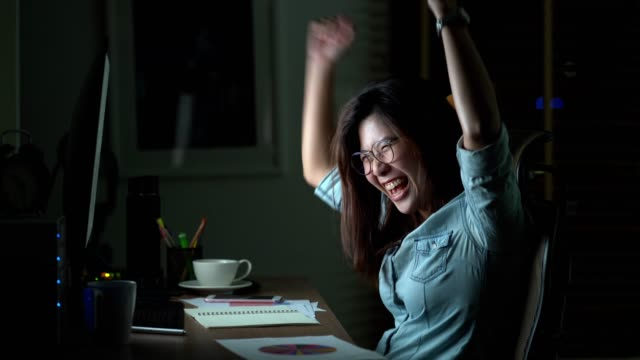 4k footage scene of attractive asian woman be happy action when working late to finished on the table in front of computer monitor desktop at workplace in the dark, work late and work hard concept - staring stock videos & royalty-free footage