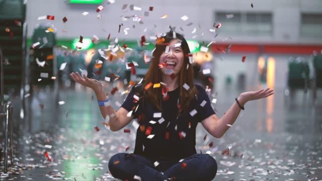 stockvideo's en b-roll-footage met 4 k beelden scène van aantrekkelijke aziatische vrouw vieren en gooien met confetti in de kamer, feest met happy new year en party concept - feliciteren