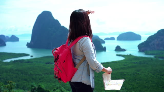 4k footage scene of Attractive Asian woman traveler looking tourist map for direction and finding destinations on the mountain at Samed Nang Chee, Nature Travel and Adventure trekking concept
