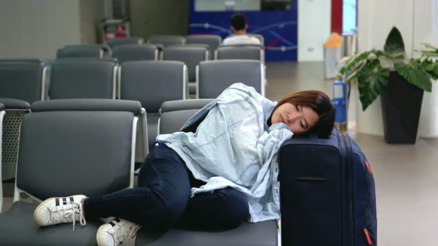 4k footage scene of Attractive Asian woman traveler sleeping with her luggage waiting flight at the airport terminal, Transportation and Passenger travel concept