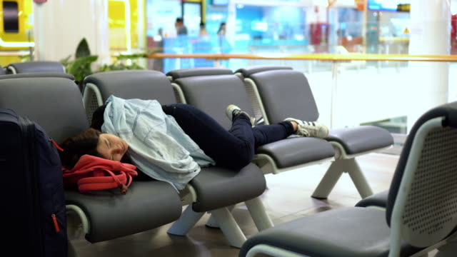 vídeos de stock e filmes b-roll de 4k footage scene of attractive asian woman traveler sleeping with her luggage waiting flight at the airport terminal, transportation and passenger travel concept - estação