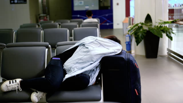 4k footage scene of attractive asian woman traveler sleeping with her luggage waiting flight at the airport terminal, transportation and passenger travel concept - uncomfortable stock videos and b-roll footage