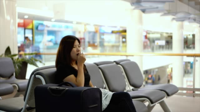 vídeos de stock e filmes b-roll de 4k footage scene of attractive asian woman traveler sleeping with her luggage waiting flight at the airport terminal, transportation and passenger travel concept - aviation fatigue