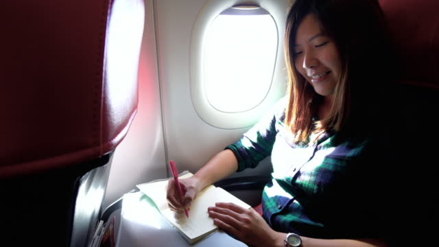 4k footage scene of attractive asian woman traveler writing her journal and diary on airplane, transportation and passenger travel concept - diary stock videos & royalty-free footage