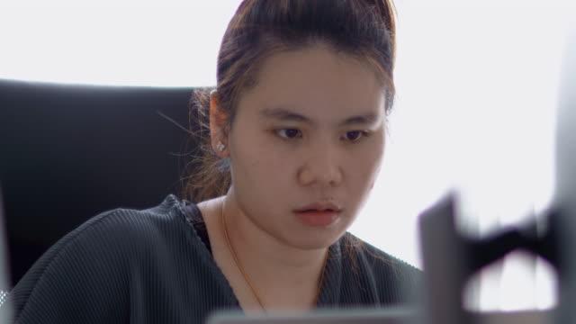 vídeos de stock, filmes e b-roll de cena de 4k de mulher asiática atraente trabalhando em casa e usando laptop no local de trabalho. - trabalhadora de colarinho branco