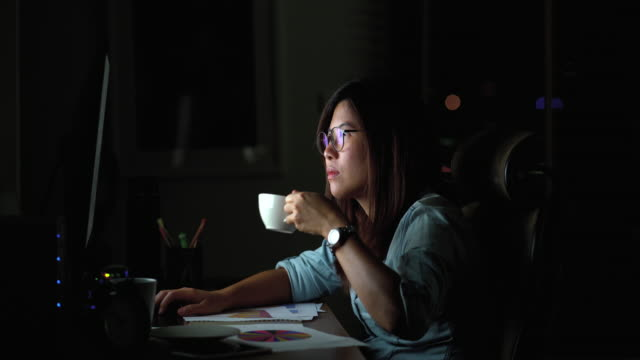 vidéos et rushes de 4 scène de séquences k de jolie femme asiatique travaillant tard et boire du café avec des mesures sérieuses sur la table en face de l'ordinateur de moniteur sur lieu de travail dans l'obscurité, travailler tard et travailler dur concept - irréductibilité