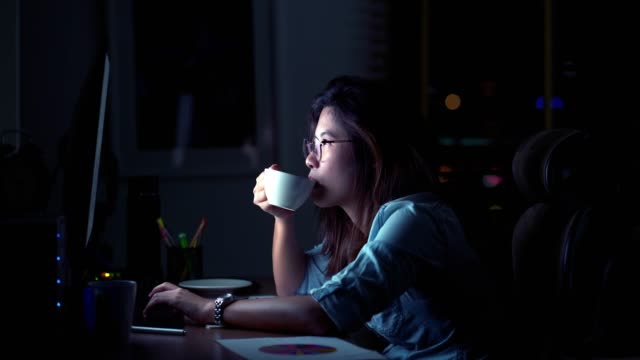 4k footage scene of attractive asian woman working late and drinking coffee with serious action on the table in front of computer monitor desktop at workplace in the dark, work late and work hard concept - low lighting stock videos & royalty-free footage